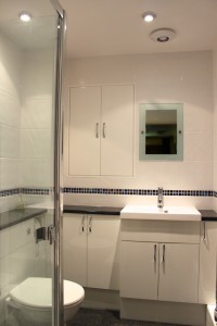 White gloss fitted bathroom units with black worktop